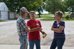 Kelly Blair, A.J.'s father, speaks with PFI members Larry and Ruth Neppl. The Neppls have been PFI members since 1988, knew A.J. as a boy and are renting some land to Kellie and A.J.