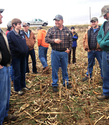 Mark Glawe speaks to a crowd at a field day in a grazed field of corn stubble cover crops
