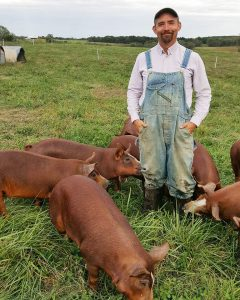 farmer stands with pastured hereford hampshire cross pigs
