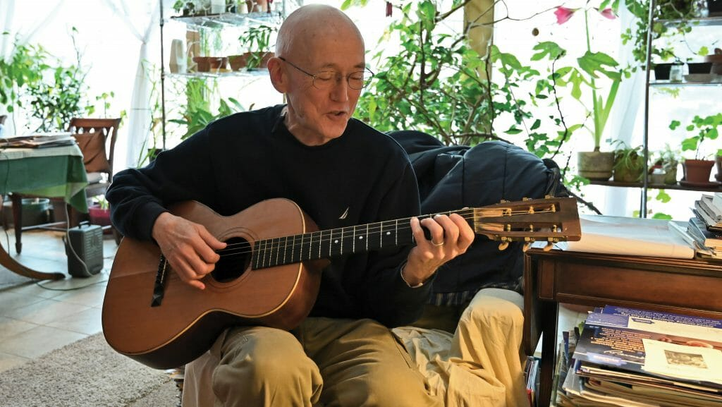 Rick Exner playing his guitar in his house