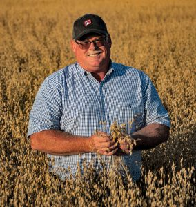 Wayne Koehler farmer in mature field of oats iowa