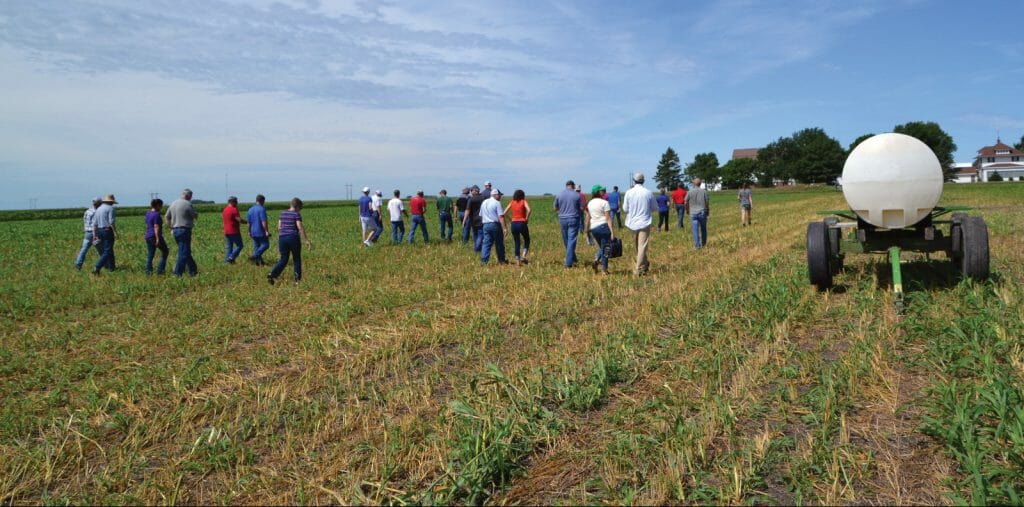 Guests at AJ and Kellie Blair field day in 2018 walk back through rye field that was baled earlier