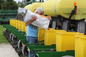Dick Sloan loads treated corn seed into his planter in May 2018
