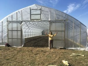 Laura Krouse standing by her newly finished high tunnel sent by Kate Edwards