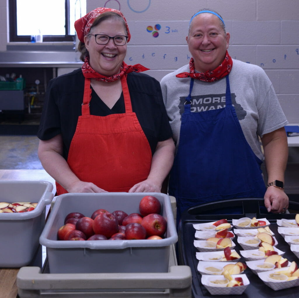 Clear Creek Amana district food director Debbie Klein (left) and Amana Elementary kitchen manager Rebecca Berstler (right) with locally grown apples