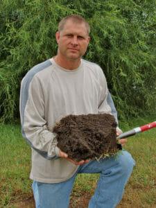 Doug Peterson holding soil sent by him
