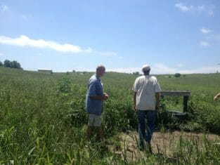 Russell Wischover and Bruce Carney look at one of the cow water sources on the farm