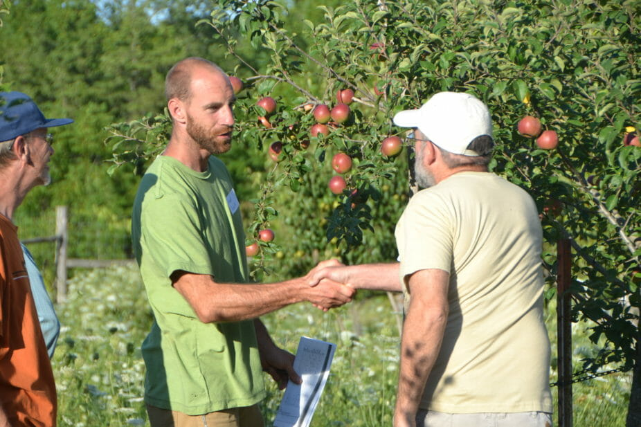 Grant Schultz and Jack Knight greet each other by an apple tree.