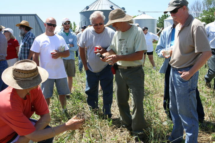 Billy leads a discussion in the field where the soybeans were drilled and the rye was rolled.