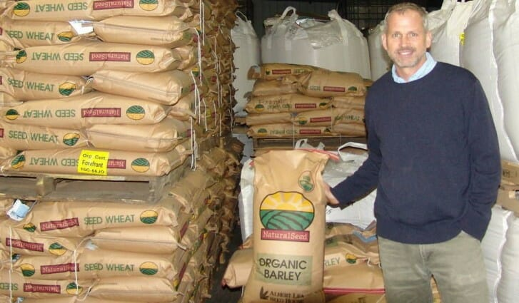 Speaker Mac Ehrhardt poses with wheat and barley seed at Albert Lea Seed House