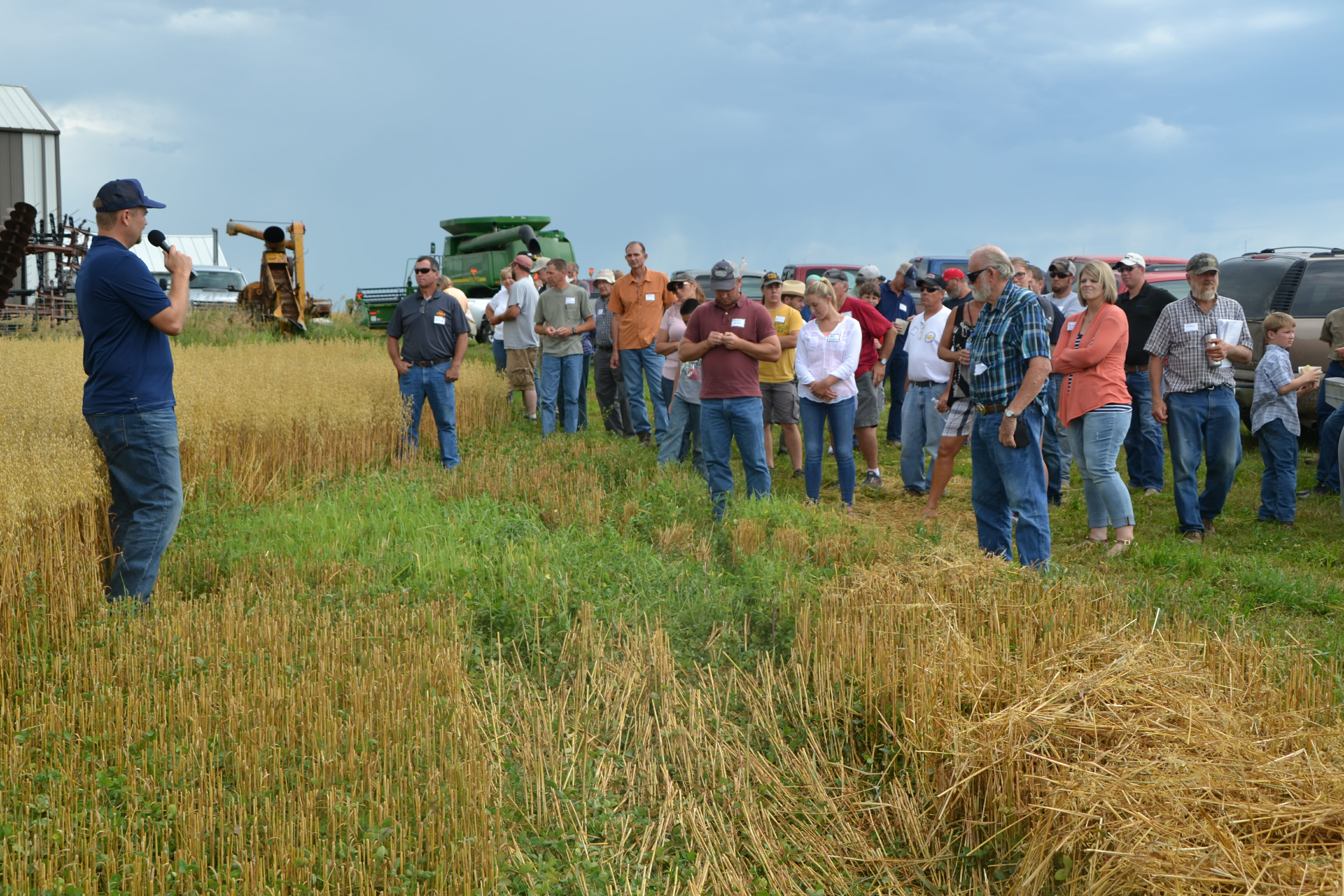Scott Ausborn (far left) discusses their oat crop with a red clover underseeding.