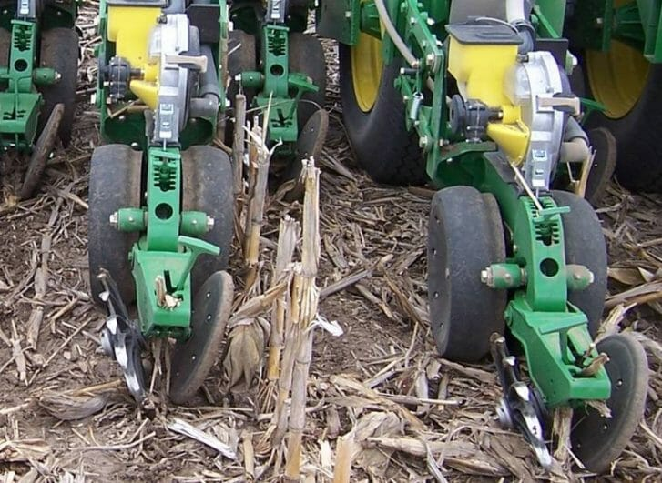 On a planter we can see two gauge wheels that cup in to a smaller diameter where they meet over the seed trench and the closing wheels show one spiked metal wheel on the left and a smooth rubbery wheel on the right.