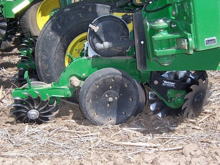 A green and black planter sits in a field of soybean stubble. On the front side of the opener discs are a spiked trash whipper wheel and coulter and to the back of the opener disks is a spiked wheel for closing the seed trench.