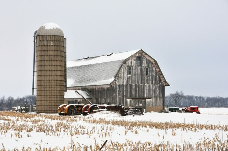 Snowy barn and silo with several tractors parked in front
