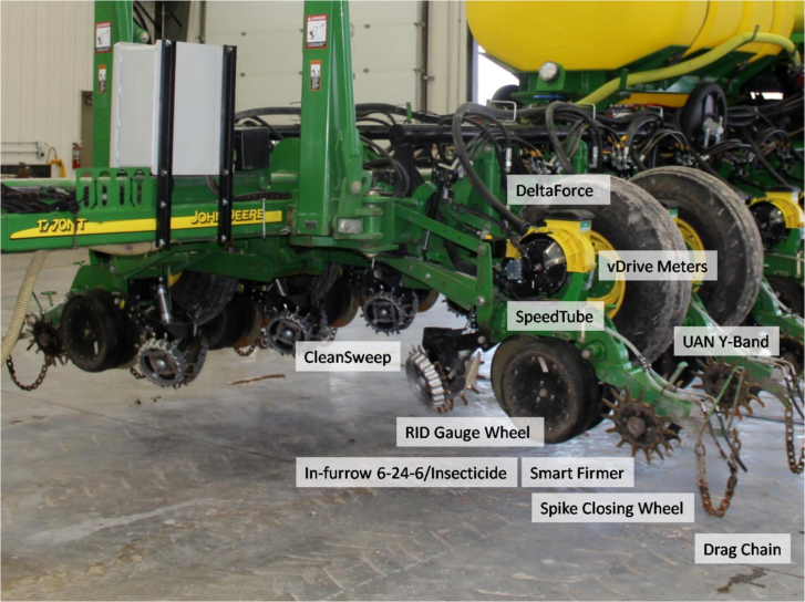 A green and yellow john deere corn planter in a shop labelled with parts such as DeltaForce, UAN Y-Band, Spiked Closing Wheel, and drag chain